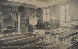 The school room of the convent at an earlier time, c.1910, School Room, Convent of the Sisters of the Poor Child Jesus', with desks, blackboards, piano etc. | Warwickshire County Record Office reference PH352/165/4