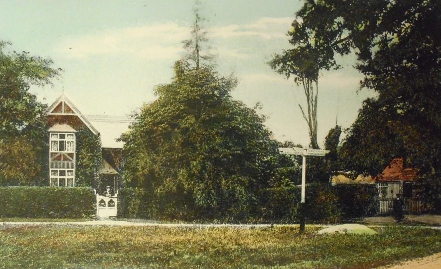 Four Ashes. Postcard, [1900]. A house is seen to the left of a large bush. In the foreground is a traditional style sign post. | Warwickshire County Record Office Reference PH352/141/4