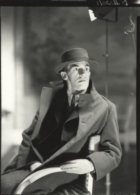John Hampson, by Howard Coster, 1935. He sits in a long coat, wearing a hat. | © National Portrait Gallery, London