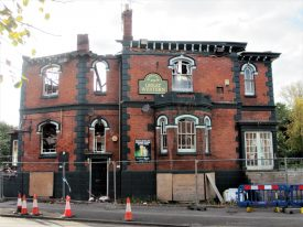 Fire-damaged Great Western pub, Coventry Road Warwick, October 2017. Two storey semi-derelict red brick building with black painted stone dressings and a bay window. The roof has gone and some of the arched windows and it is surrounded by a temporary metal fence | Image courtesy of Anne Langley