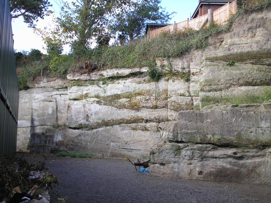Coten End Quarry, 2011. A substantial cliff face next to a path, with the top of the face covered in grass, and garden fences perched on the top. | Image courtesy of Warwickshire Museum