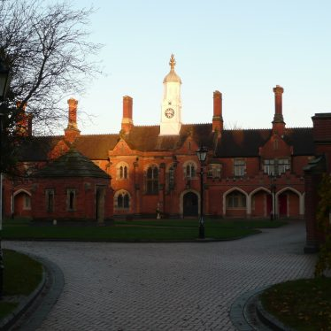 View from driveway with row of almshouses, white clock tower in middle and green in front | Image courtesy of William Arnold
