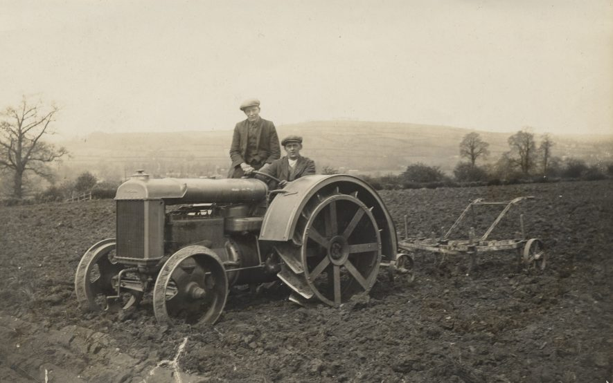 Long Compton. A tractor and plough in a field at Yerdley Farm, c.1930. The man driving the tractor is Thomas Nelson Ratcliffe, agricultural labourer, the man seated behind him is unknown. | Warwickshire County Record Office reference PH1318/2