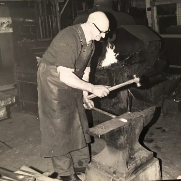 Eagle Engineering. Forge. A man hammers a strip of metal, while wearing protective goggles to shield from the heat and sparks. | Image courtesy of Susan Dyke