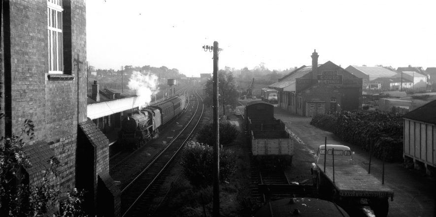 Rugby Central station viewed southward from Hillmorton Road bridge. 44830 is arriving with the evening Woodford Halse to Rugby Central local. On the right of the scene is the goods depot and Travis & Arnold timber merchants yard. | Image courtesy of theTony Newman Collection
