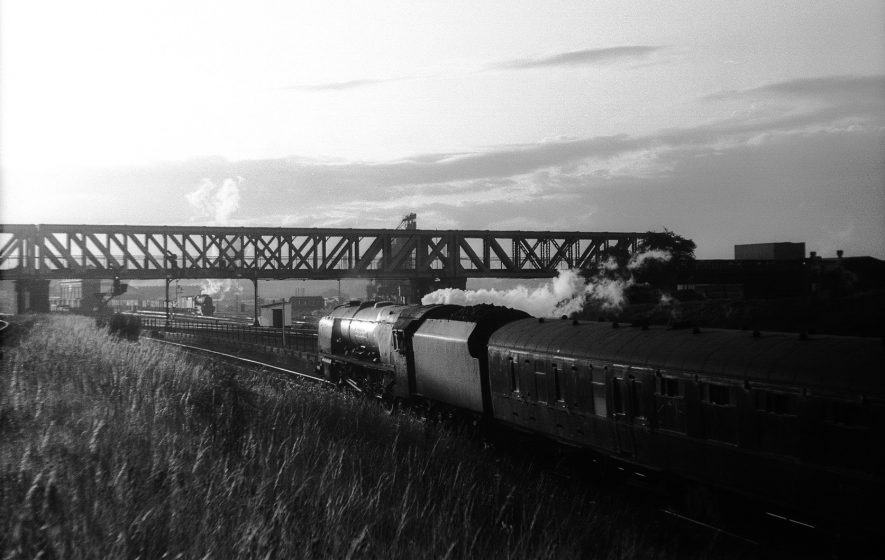 46248 'City of Leeds' approaching Rugby Midland northbound with an evening express.  In the foreground the iconic girder bridge carrying the Great Central line. The locomotive testing station is seen to the far right and Rugby Midland engine shed beyond the distant plodding 2-8-0 locomotive. | Image courtesy of the Tony Newman Collection