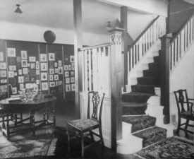 Photograph of interior of James Speight's photography studio, ground floor/waiting room [Sutton Coldfield], showing photographs on wall with stairs to right c.1908 | Warwickshire County Record Office reference CR4781/164