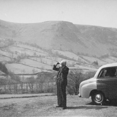 Photograph of man [James Speight] with binoculars and car [Standard 8 or 10] in front of view of hills, 1950s-1960s | Warwickshire County Record Office reference CR4781/205/1