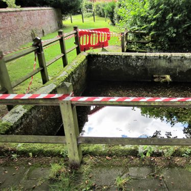 Spring at Berkswell, 2016. Water surrounded by fence and low wall with red and white striped warning tape | Image courtesy of Anne Langley