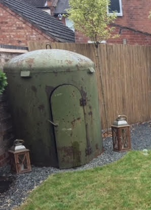 Is this an air raid shelter in Kate's garden? A green prefabricated building is bordered either side by lanterns. | Image courtesy of Kate Roffey