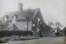 The filling station in the 1920s, when owned by FG Davies, who is believed to be in the photograph. A house is perpendicular to the road. A petrol pump is outside the house, and a man stands beside it. | Image courtesy of RT Bolton. Warwickshire County Record Office reference B.HAS.Bol(P)