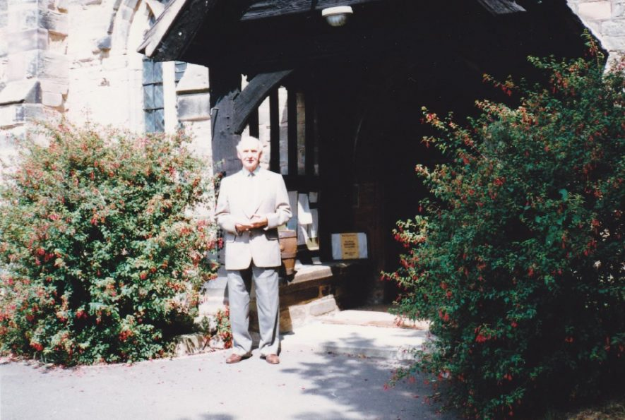 Can you help where this church is? A man stands in front of a porch, with a couple of large bushes either side of him. | Image courtesy of Patricia Wakeland
