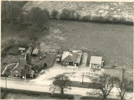 This aerial photograph of Haseley Filling Station was taken some time in the early 1960s. My first car, the grey Ford Anglia, can be seen near to the original shop.. A number of fields surround a bungalow structure. To the left is the main building and petrol station. | Image courtesy of RT Bolton. Warwickshire County Record Office reference B.HAS.Bol(P)