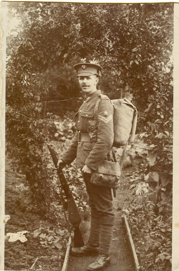 Corporal William Richard Gold, photographed at Lower Heyford, 1916. A man stands to the side, holding a rifle, and wearing a soldier's uniform. He has a moustache. | Image courtesy of RT Bolton. Warwickshire County Record Office reference B.Has.Bol(P)