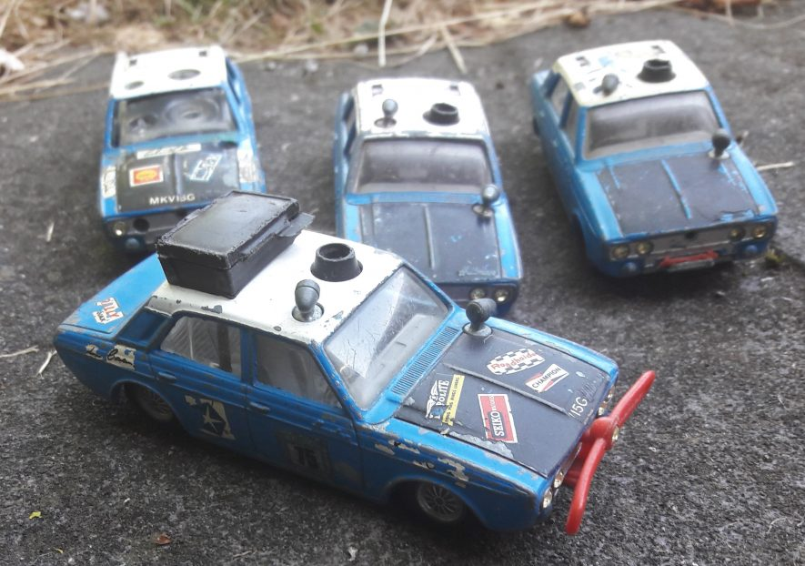 So popular it inspired a toy. A selection of Corgi Hillman Hunter rally cars, in varying states of disrepair. Four blue, white and black toy cars are on a stone slab, with dried grass behind. | Image courtesy of Benjamin Earl