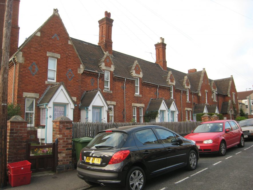 Elborough Almshouses, St.John Street, Rugby, 2018. A red brick terrace of houses with gables and porches. Cars are parked in front.   Image courtesy of Anne Langley