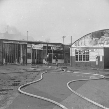 Firemen putting out the fire at the Regent Garage, 10 July 1976, showing two firemen in front of garage building with water hoses across garage yard | Image courtesy of the Leamington Courier. Warwickshire County Record Office, PH(N)600/1976/18478