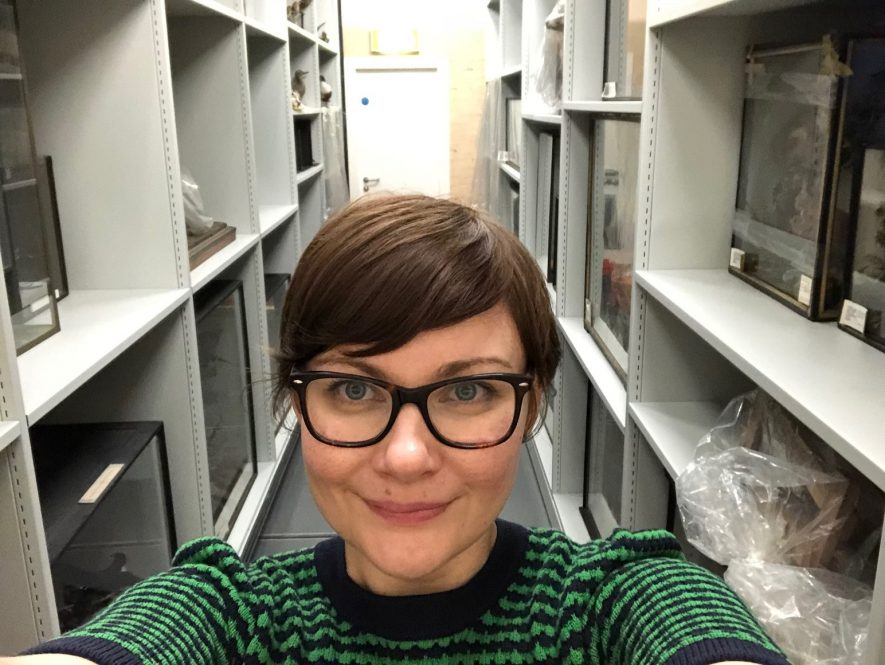 Reunited with some taxidermy that I packed and moved onto these shelves in 2013. A bespectacled woman centre of camera, white shelves run either side. | Image courtesy of Abi Flack