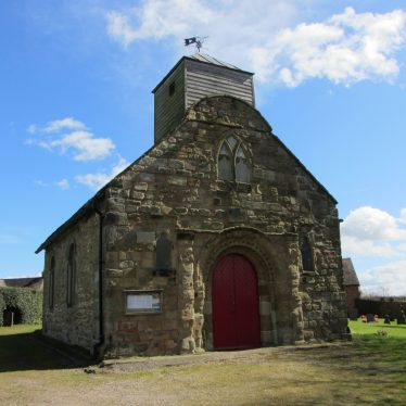 Church of St Matthew, Shuttington, 29th March 2016. A stone building with a wooden tower. A red door is centre. | Image courtesy of Angella Rodgers