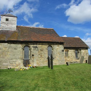 Church of St Matthew, Shuttington, 29th March 2016. A side view of a stone building, with an addition at rear. A wooden tower is atop. | Image courtesy of Angella Rodgers