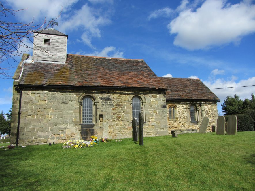 Church of St Matthew, Shuttington, 29th March 2016. A side view of a stone building, with an addition at rear. A wooden tower is atop.   Image courtesy of Angella Rodgers