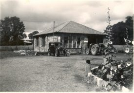 The workshop, with Austin 7 and partly dismantled Fordson N tractor at the front. In the foreground, the prolific 'Haseley Hollyhocks'. August 1950. | Image courtesy of RT Bolton. Warwickshire County Record Office reference B.HAS.Bol(P)