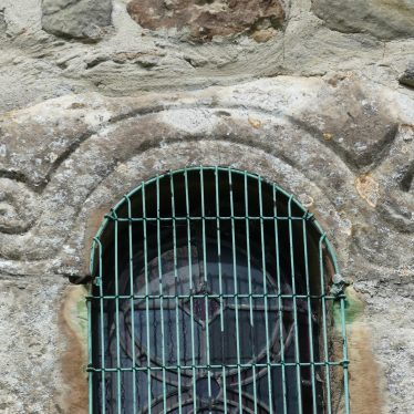 The Serpent window at St Gregory's, Offchurch, 2018. A wire mesh grille conceals the window in part, which is embedded in a stone wall. | Image courtesy of Caroline Irwin