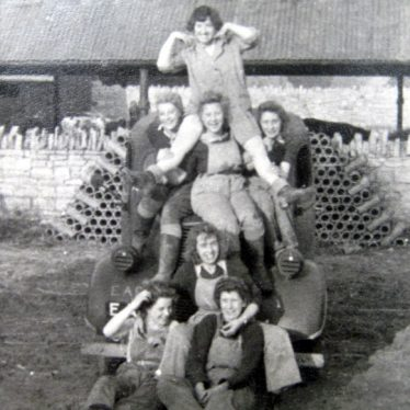 Land Army girls sitting on one of the vehicles that picked them up to go from Wickhamford Manor to Bickmarsh Hall farm. The driver was Joan Amis, who is in the front row, right hand side. 1940s. | Image courtesy of Joan Broscomb