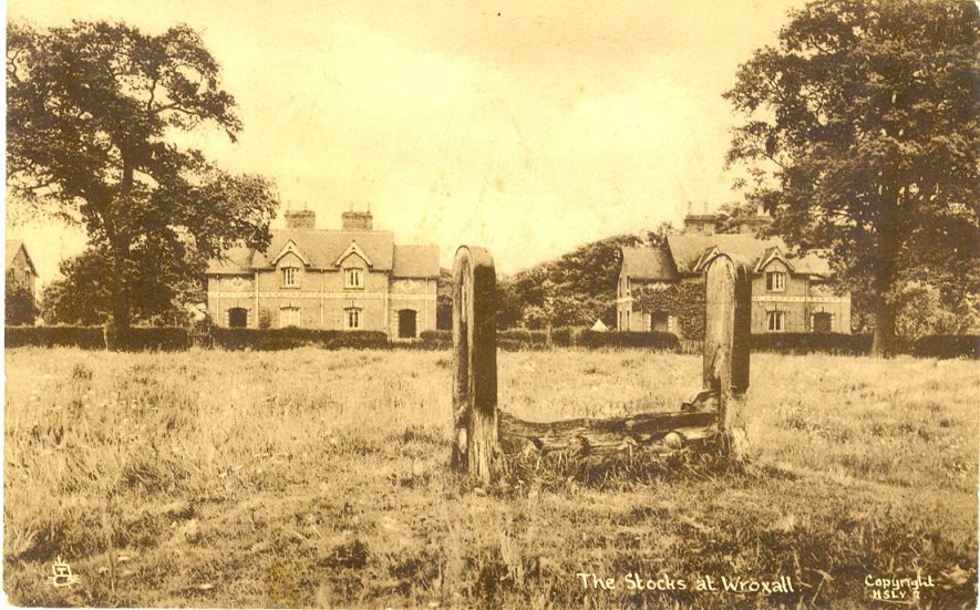 Wroxall. Postcard of the stocks on the green with houses beyond, 1950s. | Image courtesy of RT Bolton