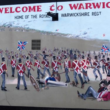 Red-coated soldiers engaged in battle with cannon, rifles and flags; one wounded man being given a drink and one body; sign for Vittle Drive cul de sac and 'Welcome to Warwick Home of the Royal Warwickshire Regt.' | Image courtesy of Anne Langley