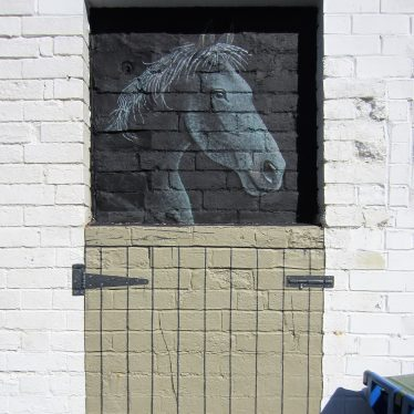 Mural of horse in stable at the 'Black Horse Inn' Warwick, 2018. A black horse is painted behind a half-door, also painted, on a brick wall | Image courtesy of Anne Langley