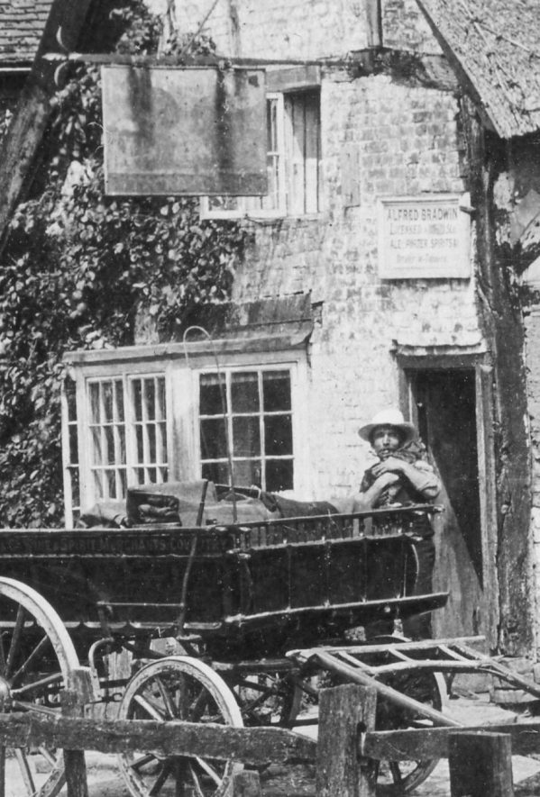 Close up of Alfred Bradwin, inn keeper of the Red Lion, Hunningham, standing by a cart and holding a cat. A figure just seen in the doorway is probably his wife, Hannah. c.1890s | Image courtesy of Pam Taylor
