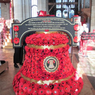Model bell covered in poppies standing on the church floor, stained glass window behind | Image courtesy of Anne Langley