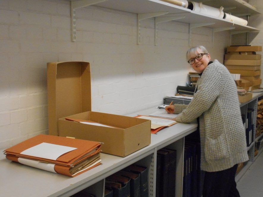 Stories, stories everywhere! Sharon working with boxes and files in the archive. Sharon stands at the worktop, going through boxes of files in the strongroom. | Image courtesy of Warwickshire County Record Office