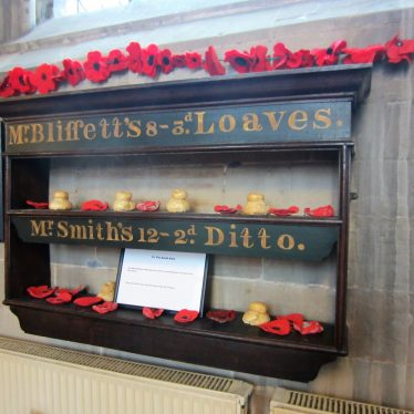 2 shelves with cottage loaves and red poppies on; one labelled 'Mr Blissett's 8 - 3d loaves', the other 'Mr Smith's 12 - 2d ditto' in St Mary's Church, Warwick | Image courtesy of Anne Langley