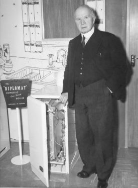 Photograph of T.F.C. ('Mr Fred') Potterton standing next to a Diplomat boiler (c.1955) | Photographer Verity Press Features, 84 Wardour Street, London. Potterton, Boiler Manufacturers collection, Warwickshire County Record Office reference CR4765/164