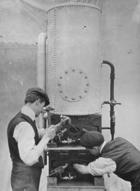 Photograph of Thomas Brooks (the uncle of Ernest G Brooks) chipping out the scale of a Victor No.13 gas fired boiler, c.1910 | Photographer H.J. Hare & Son Ltd, Lincoln Studios. Potterton, Boiler Manufacturers collection, Warwickshire County Record Office reference CR4765/165