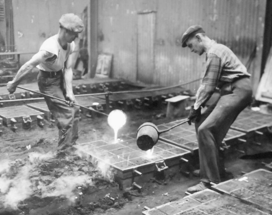 Photograph of two men hand-pouring molten metal into prepared pounds at Portobello Works, Warwick, c.1950s | Potterton, Boiler Manufacturers collection, Warwickshire County Record Office reference CR3861/97 (p.9)