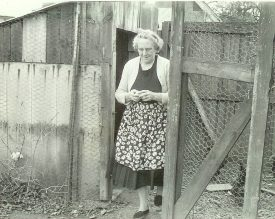 Black and white photo of woman in apron exiting a henhouse. | Photo courtesy of Sharon Forman