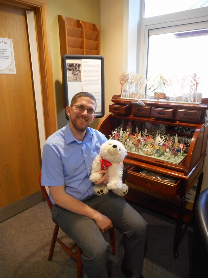 Richard Lewis, getting acquainted with Chambearlin at the County Record Office. A blue shirted gentleman sits on a chair in front of a writing desk. | Image courtesy of Meada Wadman