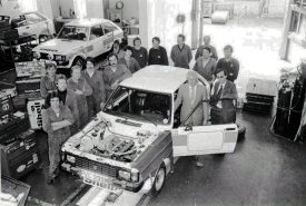 """Talbot Sunbeam Lotus Rally car in the Competitions Department, Humber Road, Coventry. Des O'Dell, Competitions Dept. Manager and Colin Cook, PR Director, behind open car door. Bernard Unett is at the back left of the car, """"striking a pose"""". 