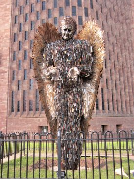 Tall statue of angel, with out-stretched hands, made out of knives, with wings made of blades, in front of pink sandstone modern cathedral | Anne Langley