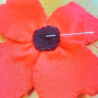 Image shows a felt, four petal poppy with red petals and a black circle inner. | Image Courtesy of Lynne Hodgson