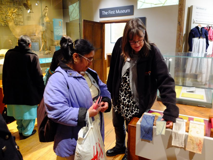 Curator Sara Wear shows a participant around Market Hall Museum for the Crossing Borders project.   Image courtesy of Heritage & Culture Warwickshire
