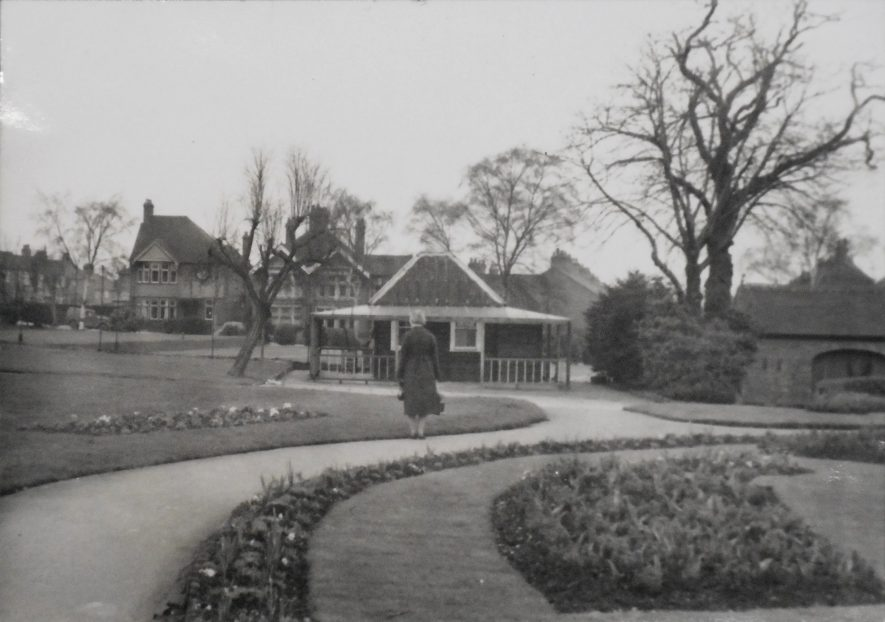 Rugby. Caldecott Park. Black and white photo of Hilda Hodges standing in the grounds of Caldecott Park, Rugby. A woman stands with her back to the camera, in front of a building, at the edge of the path. | Image Courtesy of Fern Hodges