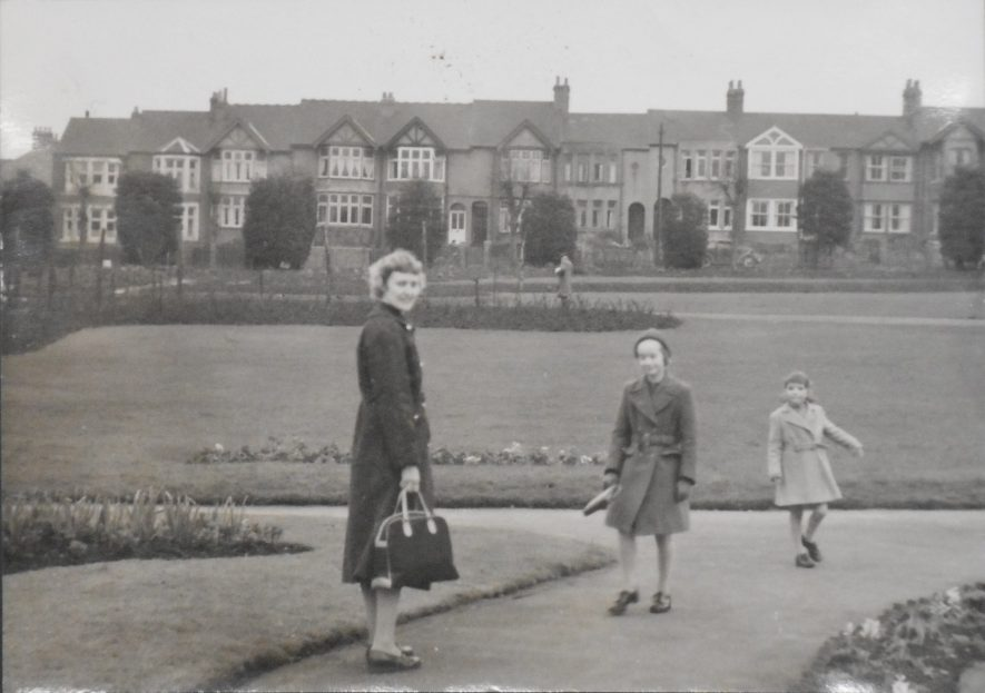Black and white photo of Hilda Hodges and her children stand on the path of the park, with houses as the backdrop. Hilda is looking back the camera while Fern and her sister are facing the camera but looking away from it. | Image Courtesy of Fern Hodges