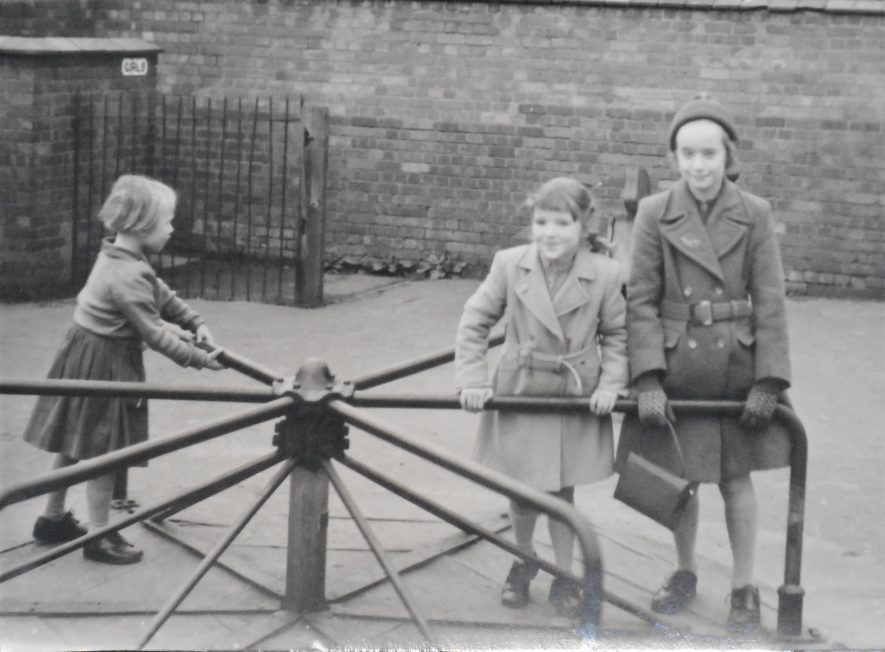 Black and white photo of Fern Hodges and her two siblings playing on the roundabout in the playground of Caldecott Park. She and one sibling are in one section facing and looking directly at the camera. Another sibling stands on the other side of the roundabout not looking at the camera. | Image Courtesy of Fern Hodges