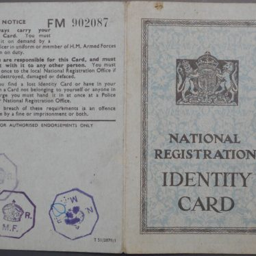 Outside cover of a National Registration Identity Card belonging to Hilda Hodges, these words are printed on the front along with the Royal Crest of the United Kingdom against a blue background. On the back there are a continuation of instructions for the use of the card, along with three official stamps. | Image Courtesy of Fern Hodges