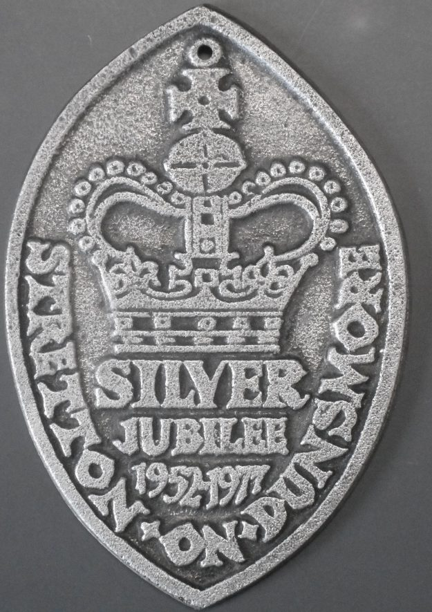 An oval shaped silver item that is embossed with the crown which has silver jubilee 1952-1977 underneath it, and Stretton-on-Dunsmore printed around it | Image Courtesy of Anne Langley