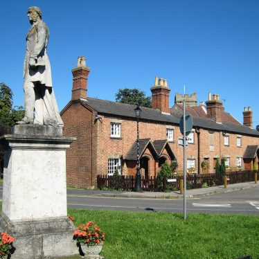 Stone statue of man on plinth with tubs of geraniums around. Row of 2-storey red brick terraced cottages behind with plaque and church tower beyond | Anne Langley